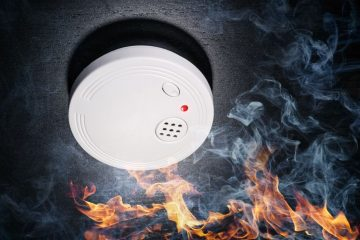 Smoke detector on the ceiling with flames and smoke